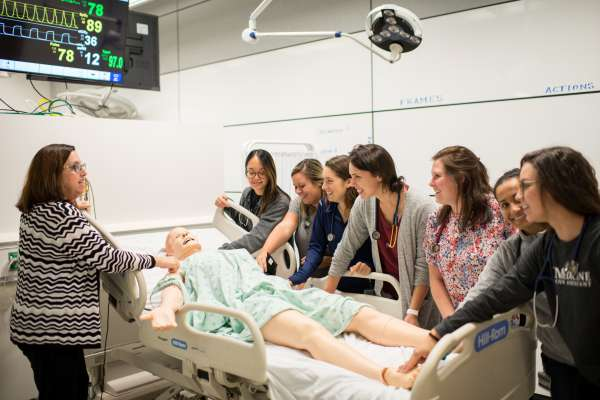 Nina Multak P-H-D teaches a group of P-A students in the simulation center using a human patient simulator in a mock hospital room within the Harrell Medical Education Building
