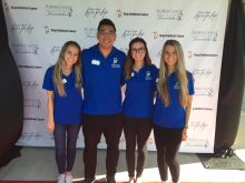 Four P-A students pose for a photo wearing matching blue polo shirts while volunteering for the The Lyrics For Life concert