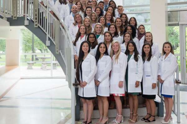 Students from the class of 2020 pose for a photo on the staircase after their white coat ceremony