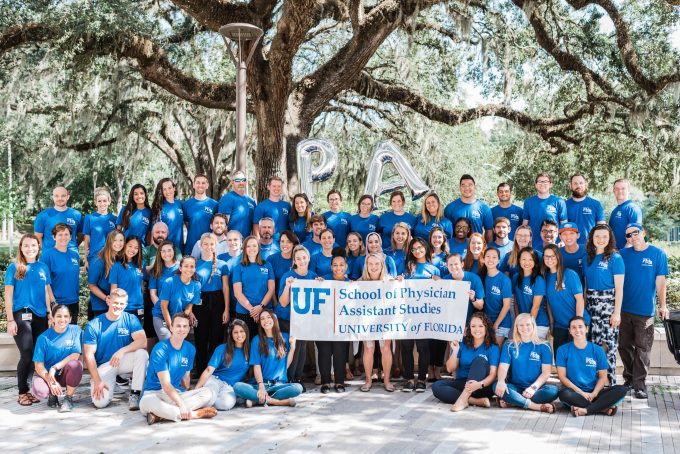 A large group of P-A students pose for a photo outside in front of a tree while holding a sign that says U-F School of Physician Assistant Studies