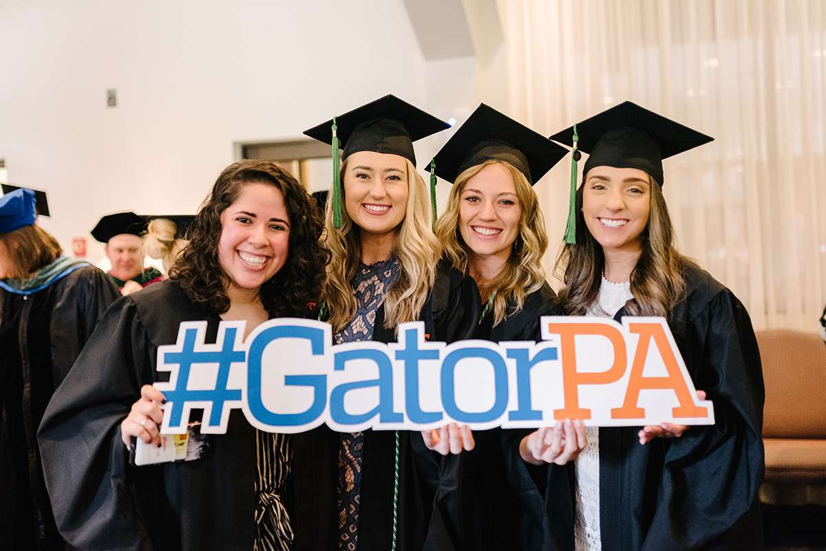 """Four graduates holding a sign that reads, """"hashtag Gator P-A."""""""